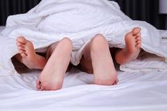 Pieds de couples vus de dessous la couverture sur le lit Image stock