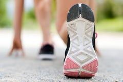 Pieds de coureur fonctionnant sur le plan rapproché de route sur la chaussure Images stock