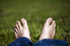 Pieds de détente sur l'herbe Images stock