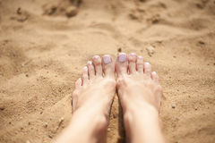 Pieds de femme avec les ongles de pied rose-clair sur le sable Photo libre de droits