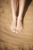 Pieds de femme avec les ongles de pied rouges sur le sable Photos libres de droits