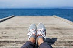 Pieds de femme dans des chaussures de sport sur le pilier en bois Photo stock