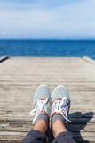 Pieds de femme dans des chaussures de sport sur le pilier en bois Photos stock