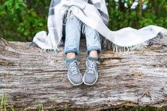 Pieds de femme dans les espadrilles et des jeans sur un rondin Photos libres de droits