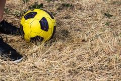 Pieds de femme dans les espadrilles et le ballon de football sur un champ sec Photographie stock libre de droits