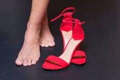 Pieds de femme et sandales rouges images stock