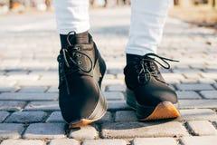Pieds de femmes dans des chaussures noires sur le trottoir un jour ensoleillé Photo libre de droits