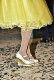 Pieds de fille dans des chaussures blanches, des bas et une robe et des confettis jaunes sur le plancher Photos libres de droits