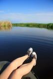 Pieds de fille dans des espadrilles sur le paysage de rivière Photo stock