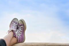 Pieds de fille et espadrilles sur le fond de ciel bleu dans les vacances Photographie stock libre de droits