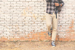 Pieds de hippie un homme et une espadrille de jeans dans le vieux mur Photographie stock libre de droits