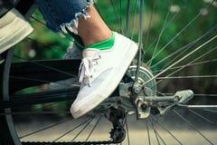 Pieds de jeune femme montant une bicyclette Images libres de droits