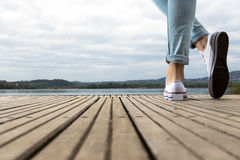 Pieds de jeune fille avec des chaussures et des blues-jean sur un pilier en bois Photos libres de droits