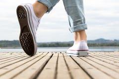 Pieds de jeune fille avec des chaussures sur un pilier en bois Image libre de droits