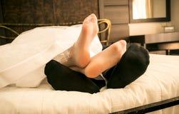 Pieds de jeunes mariées dans les bas et mariés dans les chaussettes se trouvant sur le lit Images stock