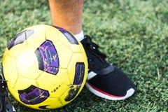 Pieds de l'homme dans les espadrilles et le ballon de football sur un champ Images stock
