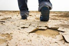Pieds de l'homme marchant sur le sol sec Images libres de droits