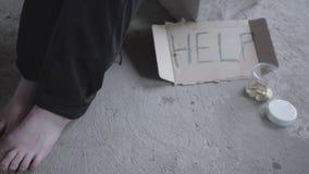 Pieds de la pauvre fille aux pieds nus s'asseyant dans un vide poussiéreux dans le bâtiment abandonné Un signe qui indique l'aide banque de vidéos