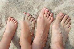 Pieds de mère de père et de leurs filles sur le sable de plage Photo stock