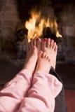 Pieds de mère et de descendant réchauffant à une cheminée Photographie stock libre de droits