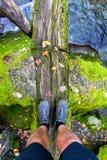 Pieds de Man's sur Moss Log Bridge photos stock