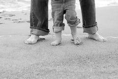 Pieds de père et d'enfant par la mer Photos stock