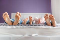 Pieds de parents et d'enfants se trouvant sur le lit Images stock