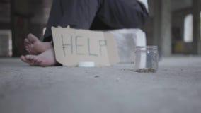 Pieds de pauvre fille aux pieds nus sur le plancher en béton Un signe brouillé qui indique l'aide et le pot avec des pièces de mo clips vidéos