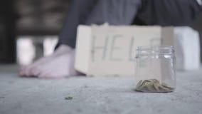 Pieds de pauvre fille aux pieds nus sur le plancher en béton Un signe brouillé qui indique l'aide et le pot avec des pièces de mo banque de vidéos