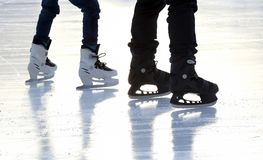 Pieds de personnes de patinage de glace de patinage sur la patinoire Images stock