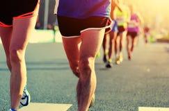 Pieds de personnes sur la route urbaine dans la course courante de marathon Photographie stock libre de droits