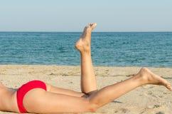 Pieds de plan rapproché de jeune fille en vacances détendant sur la plage Photographie stock libre de droits