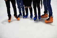 Pieds de plan rapproché du groupe de patinage de glace d'amis ensemble Photo libre de droits