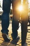 Pieds de plan rapproché et roues de bicyclette masculines méconnaissables de ville, vue arrière et activité de week-end de vacanc image stock