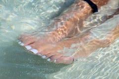 Pieds de refroidissement dans l'océan Image stock