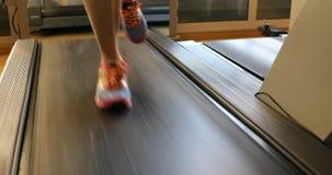 Pieds de runnig sur des tapis roulant Image stock