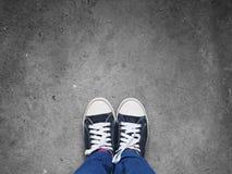 Pieds de Selfie portant les chaussures noires d'espadrilles sur le plancher Photo stock