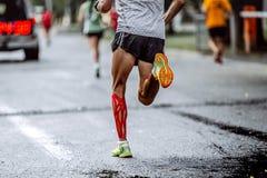 Pieds de taping masculin d'athlète sur des muscles de veau Photos stock