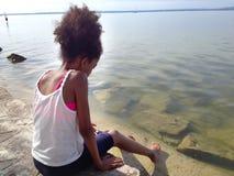 Pieds de touristes de Deeping de fille dans un lac Photographie stock libre de droits