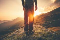 Pieds de voyageur de jeune homme seul se tenant avec des montagnes de coucher du soleil sur le fond photographie stock libre de droits