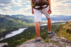 Pieds de voyageur de jeune homme seul se tenant avec des montagnes sur le backgr Image libre de droits