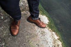 Pieds des hommes dans des jeans de lisière et de rétros chaussures Image libre de droits