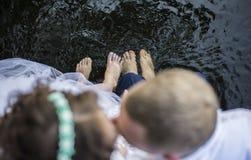 Pieds des jeunes mariés dans l'eau Photos stock