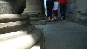 Pieds des personnes marchant le long de la colonnade du temple antique banque de vidéos