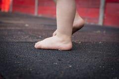 Pieds du ` s d'enfant sur le plancher première opération de chéri Photos stock