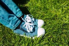 Pieds du ` s d'enfants dans les espadrilles et des jeans sur l'herbe verte Images libres de droits