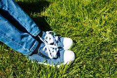 Pieds du ` s d'enfants dans les espadrilles et des jeans sur l'herbe verte Photographie stock libre de droits