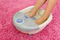 Pieds du ` s d'enfants dans un massager vibrant de pied Photo stock