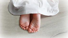 Pieds du ` s d'enfants de dessous la robe Image stock