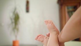 Pieds du ` s de bébé mains dans son ` s de mains et de mère banque de vidéos